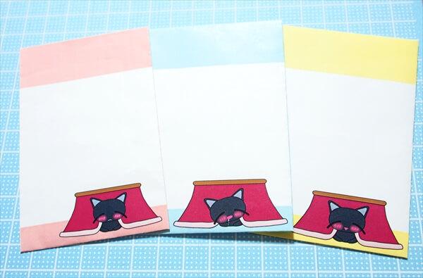 コタツでぬくぬくする黒猫のポチ袋をフリー素材として配布中