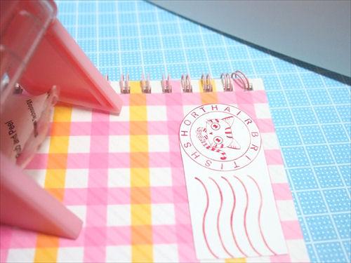 ピンクのノートに貼られた手作りの猫シール